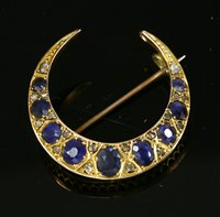 Lot 55-An Edwardian sapphire and diamond closed crescent brooch