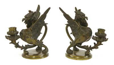 Lot 501-A pair of dark brown patinated bronze griffin/wyvern candlesticks