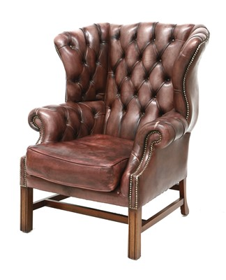 Lot 129 - A deep buttoned brown leather wing armchair