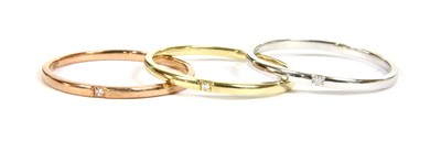 Lot 13A-A set of three white, yellow and rose gold diamond set stacking rings