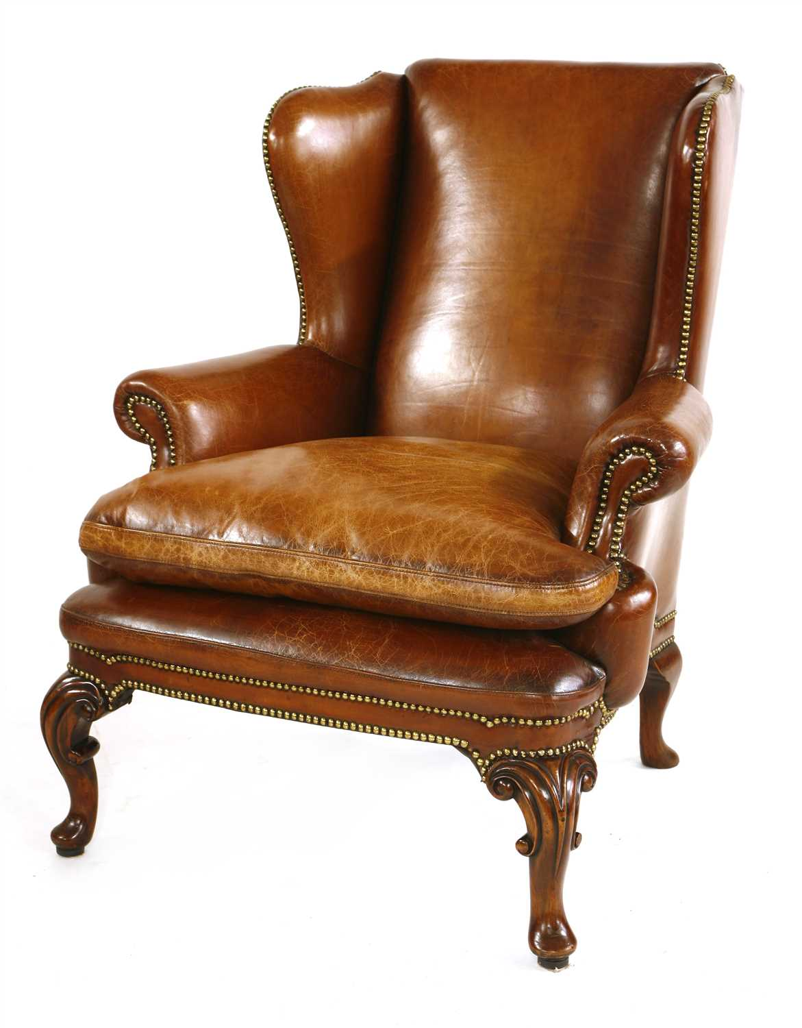 Lot 567 - A leather wing back armchair