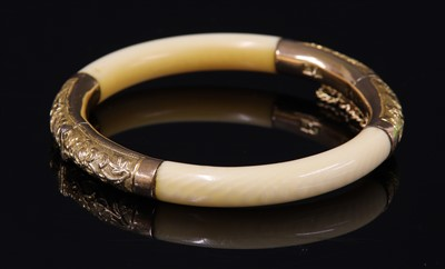 Lot 6-An early 20th century Chinese carved ivory and gold mounted hinged bangle