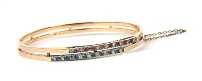 Lot 21-A French 18ct gold diamond, ruby and sapphire bangle, c.1900
