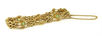 Lot 23-An Edwardian gold peridot and split pearl four row gate bracelet