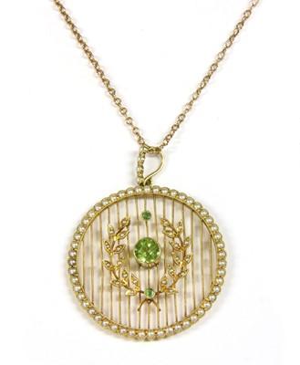 Lot 22-An Edwardian gold peridot and split pearl pendant