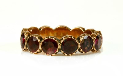 Lot 19 - A Georgian foil-backed flat cut garnet eternity-style ring
