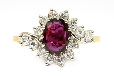 Lot 39-An 18ct gold ruby and diamond crossover cluster ring