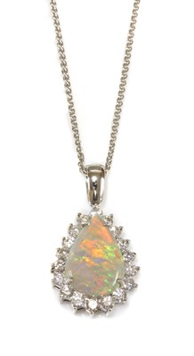 Lot 100 - A white gold opal and diamond pear-shaped cluster pendant