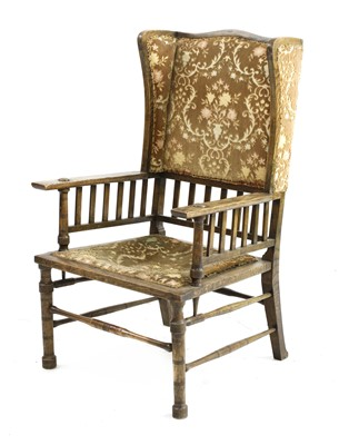 Lot 167 - An Arts and Crafts oak wingback armchair
