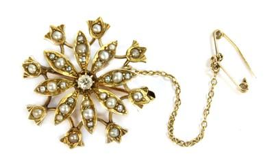 Lot 27-An Edwardian gold diamond and split pearl flower head brooch