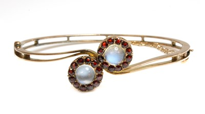 Lot 84 - A gold moonstone and garnet cluster crossover bangle