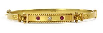 Lot 34-A gold diamond and ruby set oval hinged bangle