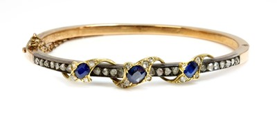 Lot 74 - A sapphire and diamond hinged bangle