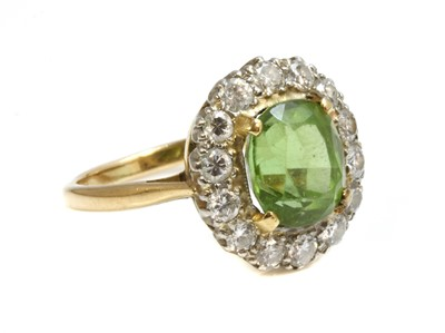 Lot 140 - A two colour gold peridot and diamond oval cluster ring
