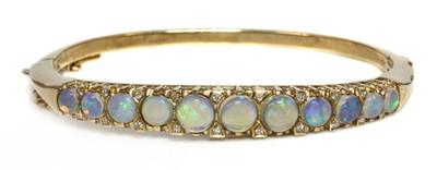 Lot 105 - A 9ct gold opal and diamond hinged bangle