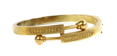 Lot 29 - A Victorian gold, Archaeological Revival, Etruscan-style crossover hinged bangle, c.1870