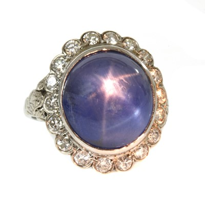 Lot 135 - An American star sapphire and diamond oval cluster ring