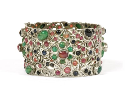 Lot 72 - A silver hinged emerald, ruby and sapphire set bangle