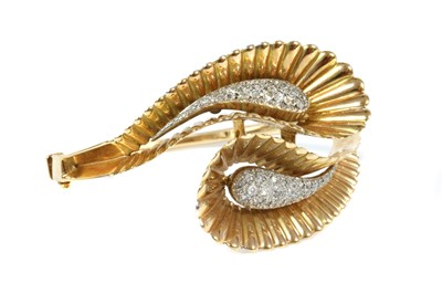 Lot 163 - A French two colour gold diamond set crossover hinged bangle, c.1940