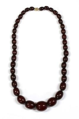 Lot 69 - A single row graduated oval oxblood coloured Bakelite bead necklace