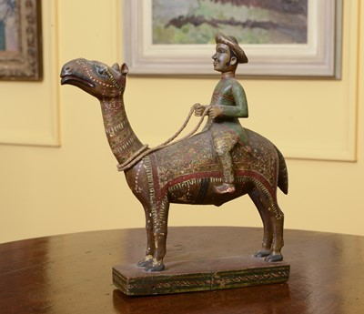 Lot 104 - A carved wooden and polychromed figure of a gentleman riding a camel