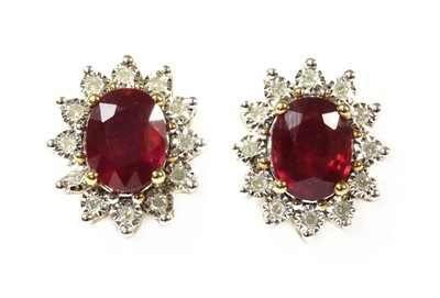 Lot 40-A pair of gold ruby and diamond cluster earrings