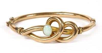 Lot 1 - A gold opal set hollow hinged bangle