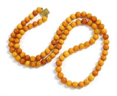 Lot 71 - A single row uniform spherical butterscotch amber bead necklace
