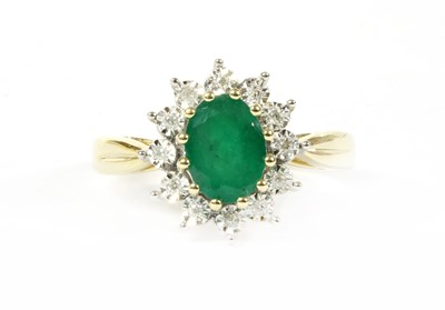 Lot 100 - A gold emerald and diamond cluster ring