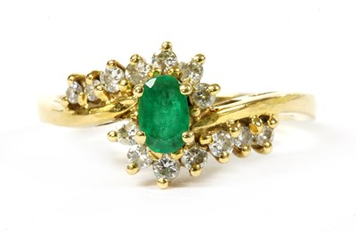Lot 112 - An 18ct gold emerald and diamond crossover cluster ring
