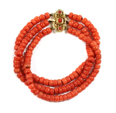 Lot 24 - A three row uniform coral bead bracelet