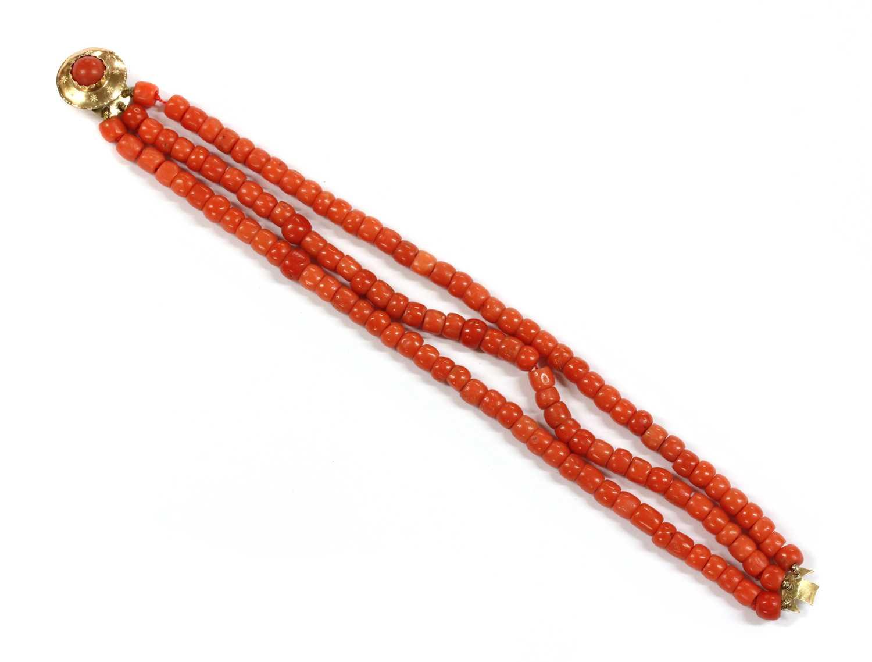 Lot 23 - A three row uniform coral bead bracelet