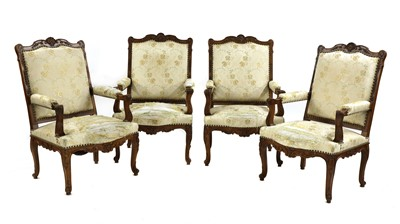 Lot 56 - A set of four French Regency-style walnut elbow chairs