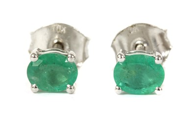Lot 123 - A pair of white gold single stone emerald stud earrings