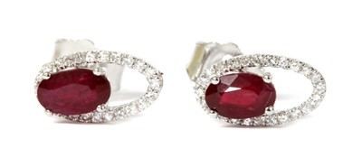 Lot 116 - A pair of white gold ruby and diamond halo stud earrings