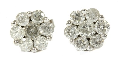 Lot 94 - A pair of white gold diamond daisy cluster earrings