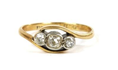Lot 47 - A gold three stone diamond crossover ring