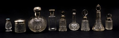 Lot 33 - A collection of cut glass silver topped scent bottles