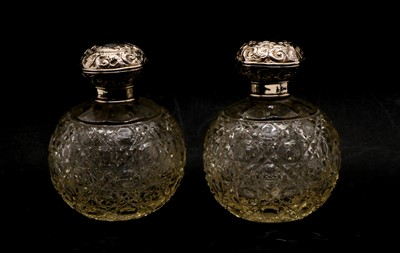 Lot 37 - A pair of globular cut glass silver topped scent bottles