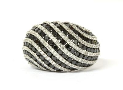 Lot 129 - A white gold black and white diamond bombé ring