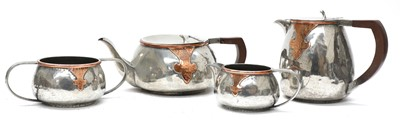 Lot 45 - An Arts and Crafts pewter and copper mounted four-piece tea set