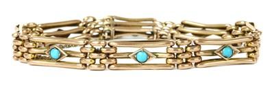 Lot 17 - An Edwardian gold turquoise set gate bracelet