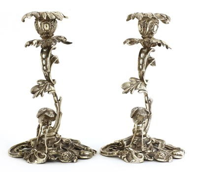 Lot 509 - A pair of cast silver-plated candlesticks