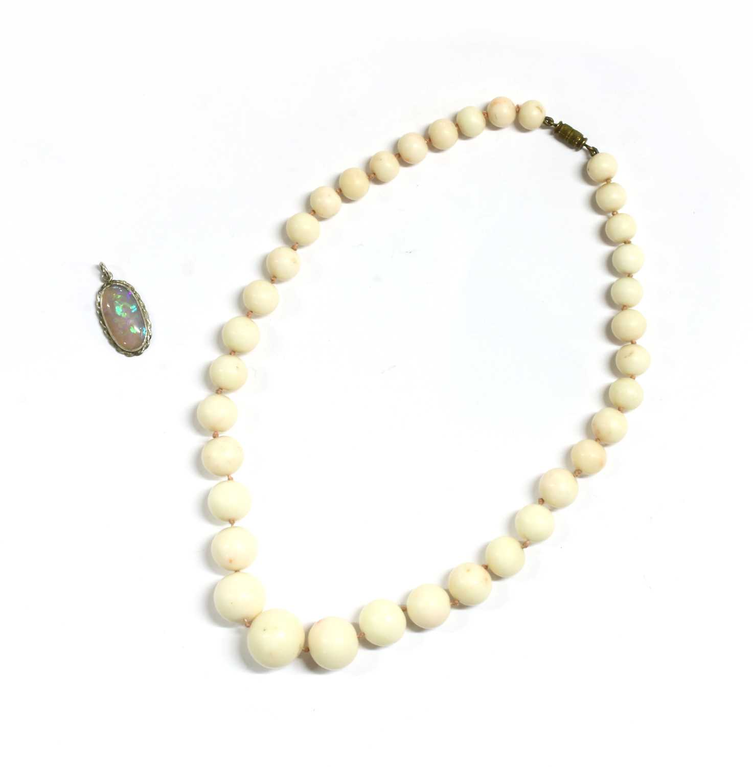 Lot 44 - A single row graduated carved white/pale pink coral necklace