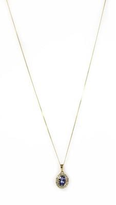Lot 172 - A gold tanzanite and diamond cluster pendant
