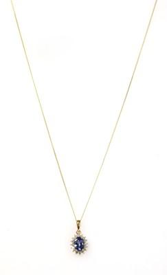 Lot 174 - A gold tanzanite and diamond cluster pendant