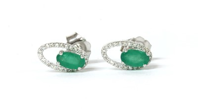 Lot 200 - A pair of white gold emerald and diamond open halo cluster stud earrings