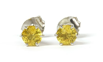 Lot 182 - A pair of white gold single stone yellow sapphire stud earrings