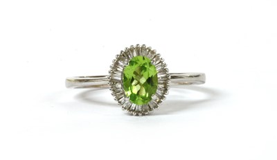 Lot 194 - A white gold peridot and diamond cluster ring