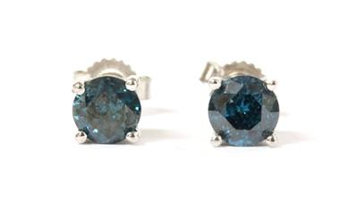 Lot 131 - A pair of white gold single stone treated blue diamond stud earrings